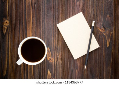 White coffee cup with black coffee ,notebook and pencil on wooden table.