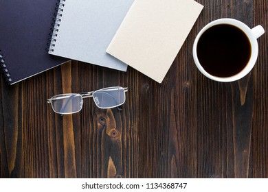 White coffee cup with black coffee ,notebooks and glasses on wooden table.