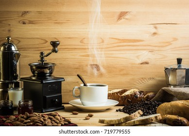 White coffee cup with coffee decoration and bread and almond on wooden background. Coffee break concept. Copyspace.