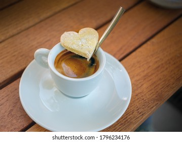 White coffee cup with espresso and cookie in the shape of heart on the wooden table.