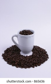White coffee cup filled with roasted coffee beans and encircled with roasted beans.