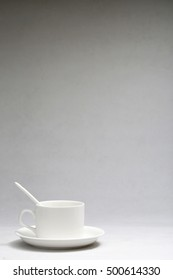 White coffee cup in front of the grey background