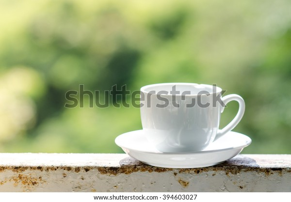 White coffee cup with green bokeh.