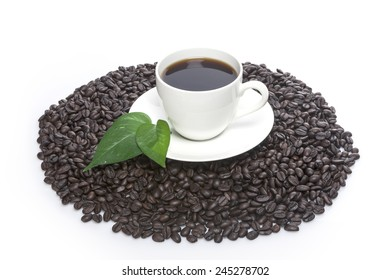 white coffee cup and green leaf(leaves) on the coffee beans isolated white at the studio.