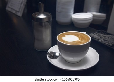 White coffee cup with heart shape latte or cappucino in coffee bar.