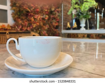 white coffee cup with lipstick marks, blur beautiful decorated coffee shop background - autumn style