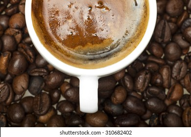 White coffee cup on coffee beans background.
