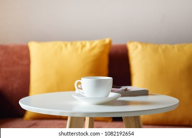 White coffee cup on the table in livingroom interior with orang color shade fabric sofa and pillows with copy space