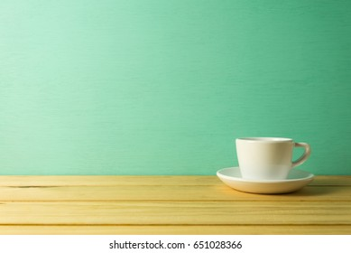 White coffee cup on table over green wooden background with copy space