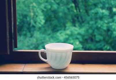 White coffee cup on a window sill (retro style)