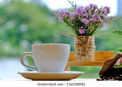 white coffee cup on wooden have green leaf and black cofffee beans on table front off flowers.