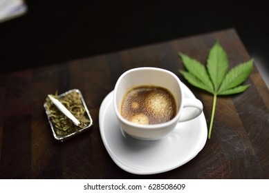 white coffee cup on wooden butcher cutting board with joint, cannabis bud and cannabis leaf