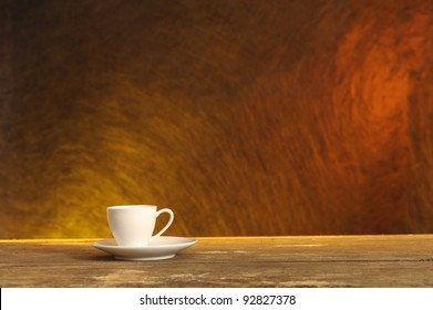 white coffee cup on wooden table, orange structured background