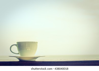 White coffee cup with outdoor view - Vintage Filter