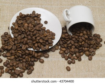white coffee cup and plate stacked with whole coffee beans