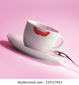White coffee cup with red lipstick mark on pink background