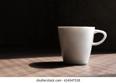 white coffee cup and shadow on wood table