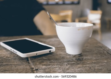 white coffee cup with smart phone on table in cafe