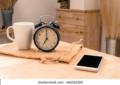 white coffee cup, smartphone and black retro alarm clock times at 7 o'clock morning on wooden table, selective focus, copy space, vintage color tone