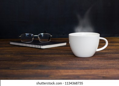 White coffee cup with smoke ,glasses and notebook.