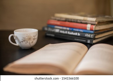 White Coffee cup and some books on the table.