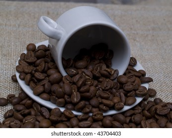 white coffee cup stacked with whole coffee beans