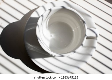 white coffee cup with striped shadows