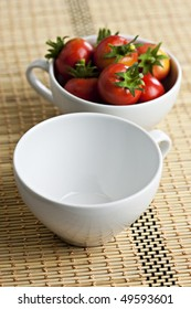 White Coffee Cups With Cherry Tomatoes on Placemat