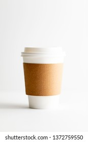 White coffee to go cup with a cardboard sleeve on a bright background