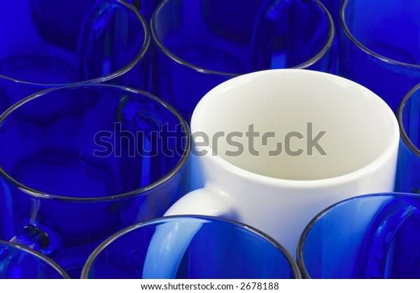 White coffee mug amongst blue glass mugs - horizontal format