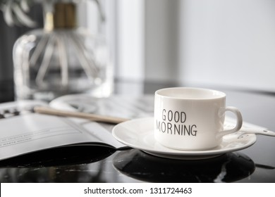 White coffee mug with bouquet of flowers lily of the valley and notes 'good morning' on black modern marble table. Beautiful sunshine morning refreshment.