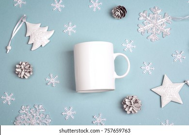 White coffee mug  with Christmas decorations on blue background. Top view, flat lay. Space for text or design.