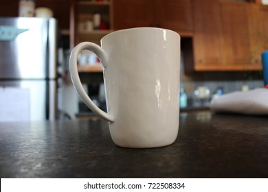 White coffee mug cup sitting on dark granite counter top in kitchen