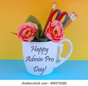 A white coffee mug filled with office supplies like pencils and a pair of scissors with a couple of silk roses on a blue and yellow background. Happy administrative professional'??s day message