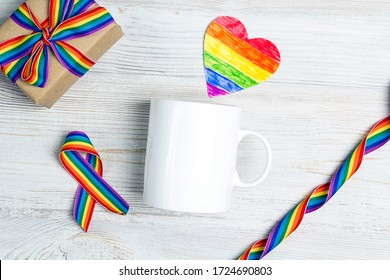 White coffee mug and gift with rainbow LGBT ribbon on a light wooden background. Space for text or design. Homosexual and lgbt concept.