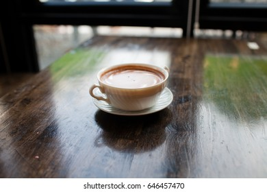 White coffee mug lay on wooden background.