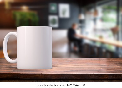 White coffee mug mockup in a cafe on  a wooden table top.  Great for overlaying your custom quotes and designs for selling mugs.