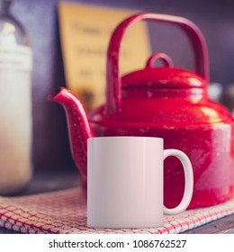 White coffee Mug Mockup in a kitchen setup with a red kettle. Great for overlaying your custom quotes and designs for selling mugs.