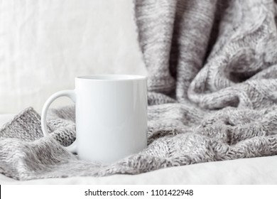 White coffee mug mockup on the bed with gray blanket