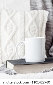 White coffee mug mockup on the bed with gray blanket and book