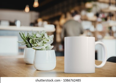 White coffee Mug Mockup set-up in a cafe, next to cactus plants and with blurred background. Great for overlaying your custom quotes and designs for selling mugs.