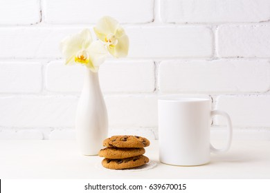 White coffee mug mockup with soft yellow orchid in vase and cookies.  Empty mug mock up for design promotion.