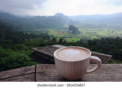 White Coffee Mug Put on the table. A coffee mug with a natural back view. Concept of vacation. Phu Langka Forest Park is a famous tourist attraction of  Phayao, Thailand.