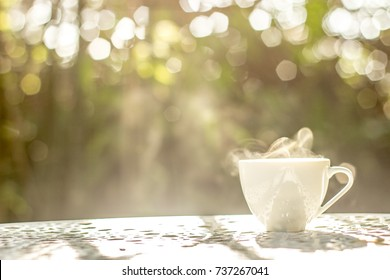 A white of coffee on white table in the garden, coffee break in the morning with light bokeh , relaxing and refreshing concepts.