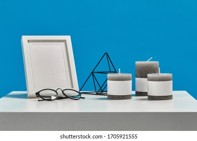 White coffee table with empty photo frame, three candles, decorative iron triangle and black rimmed glasses. Blue background. Close up, copy space