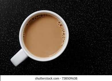 White coffee or tea with bubbles in white ceramic mug isolated on black granite table from above.