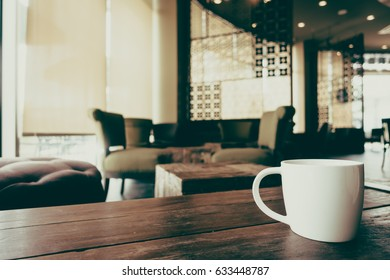 White cofffee cup on wooden table in coffee shop cafe - Vintage Filter