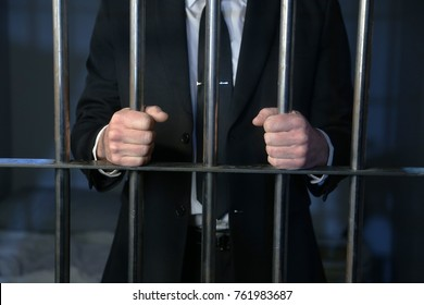 A white collar criminal behind bars after being arrested for banking crimes