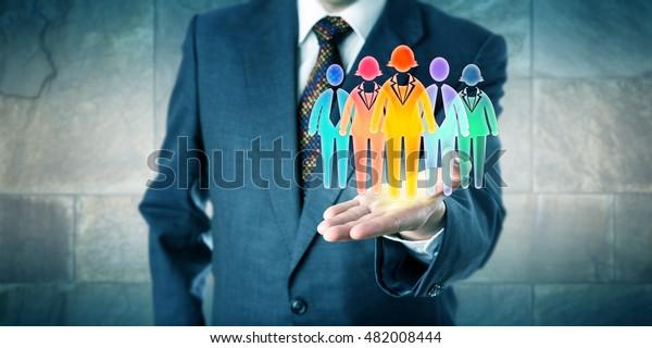 White Kragen Manager präsentiert ein Team von fünf mehrfarbigen Arbeiter-Icons in der offenen Handfläche seiner linken Hand. Geschäftskonzept für Teambuilding, Diversitätsintegrationskultur und Personalausstattung.