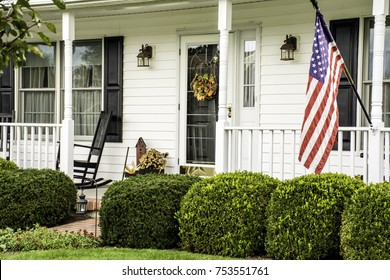 white colonial home decorated for fall with American flag flying from front porch with rocking chairs